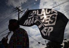 FILE - In this Dec. 12, 2020, file photo, MD Crawford carries a Black Lives Matter flag before a march in La Marque, Texas to protest the shooting of Joshua Feast, 22, by a La Marque police officer. A financial snapshot shared exclusively with The Associated Press shows the Black Lives Matter Global Network Foundation raked in just over $90 million last year. (Stuart Villanueva /The Galveston County Daily News via AP, File)