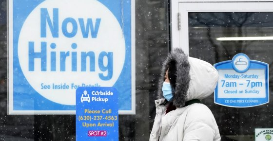 """FILE - In this Feb. 6, 2021, file photo, a woman walks past a """"Now Hiring"""" sign displayed at a CD One Price Cleaners in Schaumburg, Ill. U.S. employers added a surprisingly robust 379,000 jobs in February in a sign the economy is strengthening as virus cases drop, vaccinations ramp up, Americans spend more and states ease business restrictions. (AP Photo/Nam Y. Huh, File)"""