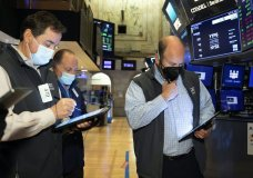 In this photo provided by the New York Stock Exchange, traders work on the floor, Wednesday April 14, 2021. U.S. stock indexes are tacking a bit more onto their record highs in midday trading Wednesday after big banks kicked off a highly anticipated earnings reporting season with profits that thundered past Wall Street's expectations. (Colin Ziemer/New York Stock Exchange via AP)