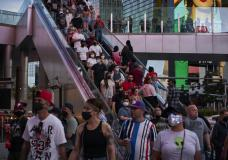 People ride an escalator along the Las Vegas Strip, Saturday, April 24, 2021, in Las Vegas. Las Vegas is bustling again after casino capacity limits were raised Saturday, May 1, to 80% and person-to-person distancing dropped to 3 feet (0.9 meters). (AP Photo/John Locher)