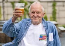 """In this May 6, 2021 photo, George Ripley, 72, of Washington, holds up his free beer after receiving the J & J COVID-19 vaccine shot, at The REACH at the Kennedy Center in Washington. Free beer is the latest White House-backed incentive for Americans to get vaccinated for COVID-19. President Joe Biden is expected to announce a """"month of action"""" on Wednesday to get more shots into arms before the July 4 holiday. (AP Photo/Jacquelyn Martin)"""