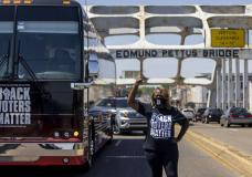 LaTosha Brown, co-founder of Black Voters Matter, stands atop the Edmund Pettus Bridge, a famous civil rights landmark, Saturday, May 8, 2021, in Selma, Ala. Brown was a keynote speaker at the John Lewis Advancement Act Day of Action, a voter education and engagement event held in Selma and Montgomery. (AP Photo/Vasha Hunt)