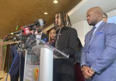 Messiah Young speaks during a news conference accompanied by attorney L. Chris Stewart, right, who represents plaintiff Taniyah Pilgrim, background center, in Atlanta on Thursday, June 17, 2021. Young and Pilgrim were pulled from their car on May 30, 2020 by Atlanta police and are suing the city and officers for excessive force. Atlanta police had no justification for pulling the two students from their car and hitting them with stun guns while they were stuck in traffic caused by protests over George Floyd's death, the lawsuit announced Thursday claims. (AP Photo/Sudhin Thanawala)