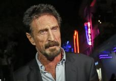 FILE — In this Dec. 12, 2012, file photo, anti-virus software founder John McAfee answers questions to reporters as he walks on Ocean Drive, in the South Beach area of Miami Beach, Fla. McAfee, the outlandish security software pioneer who tried to live life as a hedonistic outsider while running from a host of legal troubles, was found dead in his jail cell near Barcelona, Spain, on Wednesday, June 23, 2021. His death came just hours after a Spanish court announced that it had approved his extradition to the United States to face tax charges punishable by decades in prison, authorities said. (AP Photo/Alan Diaz, File)