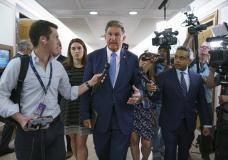 Sen. Joe Manchin, D-W.Va., chairman of the Senate Energy and Natural Resources Committee, talks to reporters as he arrives for a hearing on infrastructure needs of the U.S. energy sector, western water and public lands, at the Capitol in Washington, Wednesday, June 23, 2021. Manchin and other Senate infrastructure negotiators are meeting with President Joe Biden at the White House later today. (AP Photo/J. Scott Applewhite)