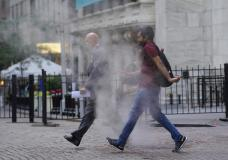 People walk through steam from a street grating outside the New York Stock Exchange, Wednesday, June 16, 2021. Stocks are off to a mixed start on Wall Street as traders wait for the latest U.S. monthly jobs report due out Friday, July 2. The S&P 500 was little changed in the early going Wednesday, June 30. (AP Photo/Richard Drew)