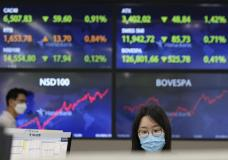 A currency trader watches monitors at the foreign exchange dealing room of the KEB Hana Bank headquarters in Seoul, South Korea, Thursday, July 1, 2021.Asian shares are mostly lower as investors await a much watched U.S. jobs for indications of how the recovery from the pandemic is faring. (AP Photo/Ahn Young-joon)