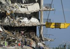 A crane is used to remove sets of human remains, as search and rescue personnel work atop the rubble at the Champlain Towers South condo building, where scores of people remain missing more than a week after it partially collapsed, Friday, July 2, 2021, in Surfside, Fla. Rescue efforts resumed Thursday evening after being halted for most of the day over concerns about the stability of the remaining structure.(AP Photo/Mark Humphrey)