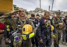 A member of the Israeli search and rescue team, left, salutes in front of the rubble that once was Champlain Towers South during a prayer ceremony, Wednesday, July 7, 2021, in Surfside, Fla. Members of search and rescue teams and Miami-Dade Fire rescue, along with police and workers who have been working at the site of the collapse gathered for a moment of prayer and silence next to the collapsed tower. (Jose A Iglesias/Miami Herald via AP)