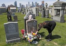 FILE - In this Sunday, May 10, 2020 file photo, Sharon Rivera adjusts flowers and other items left at the grave of her daughter, Victoria, at Calvary Cemetery in New York, on Mother's Day. Victoria died of a drug overdose in Sept. 22, 2019, when she just 21 years old. According to a report released by the Centers for Disease Control and Prevention on Wednesday, July 14, 2021, drug overdose deaths soared to a record 93,000 last year in the midst of the COVID-19 pandemic. (AP Photo/Kathy Willens, File)