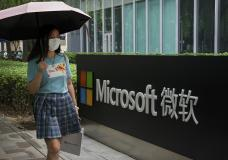 A woman wearing a face mask to help curb the spread of the coronavirus walks by the Microsoft office building in Beijing, Tuesday, July 20, 2021. The Biden administration and Western allies formally blamed China on Monday for a massive hack of Microsoft Exchange email server software and asserted that criminal hackers associated with the Chinese government have carried out ransomware and other illicit cyber operations. (AP Photo/Andy Wong)