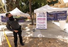 A private security guard gives directions to people looking to get vaccinated, as banners advertise the availability of the Johnson & Johnson and Pfizer COVID-19 vaccines at a county-run vaccination site offering free walk-in with no appointment needed at the Eugene A. Obregon Park in Los Angeles Thursday, July 22, 2021. The top health official in Los Angeles County on Thursday implored residents to get vaccinated as the region experiences a coronavirus surge similar to last summer's. (AP Photo/Damian Dovarganes)