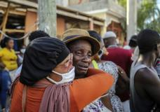 People cry during the search for those who are still missing in a house destroyed by the earthquake in Les Cayes, Haiti, Sunday, Aug. 15, 2021. The death toll from a magnitude 7.2 earthquake in Haiti climbed to more than 1,200 on Sunday as rescuers raced to find survivors amid the rubble ahead an approaching tropical storm. (AP Photo/Joseph Odelyn)