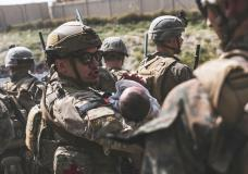 In this image provided by the U.S. Marine Corps, an Airmen comforts an infant during an evacuation at Hamid Karzai International Airport in Kabul, Afghanistan, Friday, Aug. 20, 2021. (Sgt. Isaiah Campbell/U.S. Marine Corps via AP)