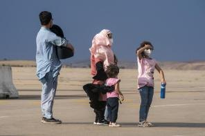 An Afghan family wait on the runway after disembarking a plane from Afghanistan, at the Torrejon military base as part of the evacuation process in Madrid, Monday. Aug. 23, 2021. (AP Photo/Andrea Comas)