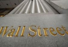 FILE - In this Nov. 5, 2020 file photo, a sign for Wall Street is carved in the side of a building, in New York. Stocks are opening slightly higher on Wall Street Friday, Oct. 1, 2021 a day after closing out September with their first monthly loss since January. (AP Photo/Mark Lennihan, File)