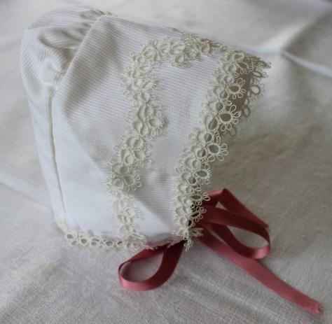 Kyse til dåpskjole sydd av Oddlaug Juberg Kvamme pyntet med nuppereller laget av Nora Kvamme