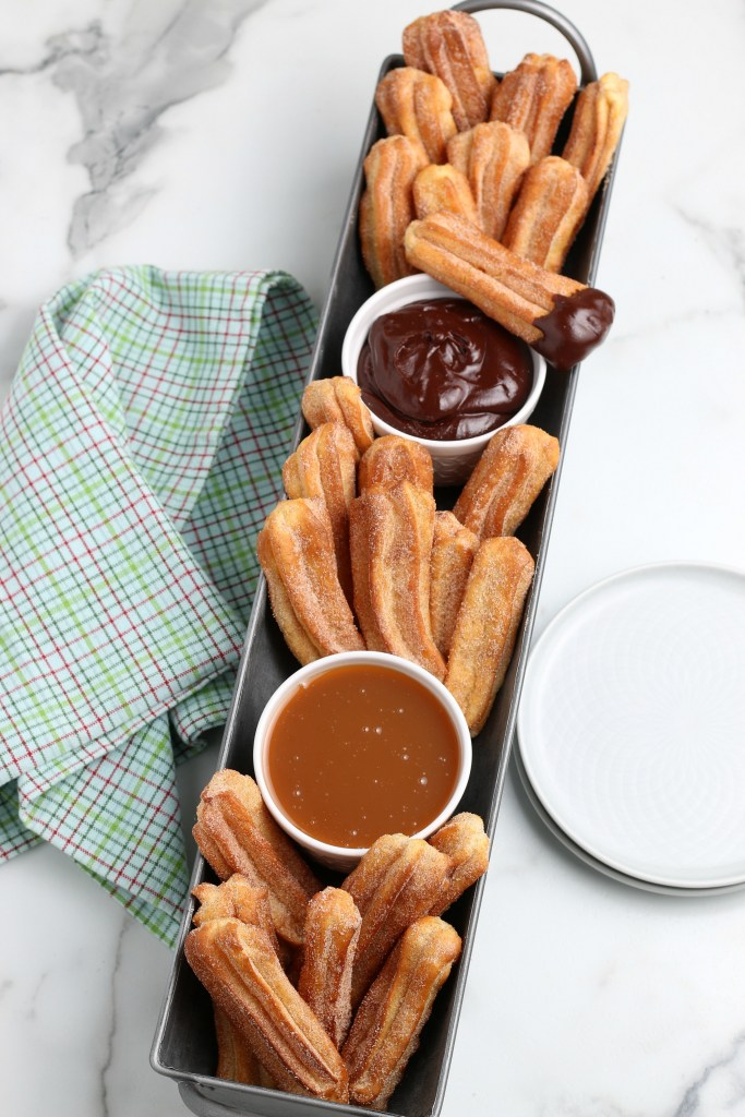 air fryer churros in a silver tray with dipping sauces