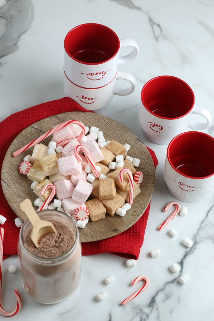 jar of hot chocolate mix with christmas mugs and plate of treats