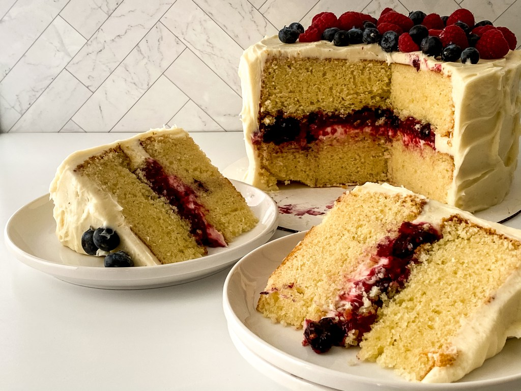 two slices of mixed berry chantilly cake on plates