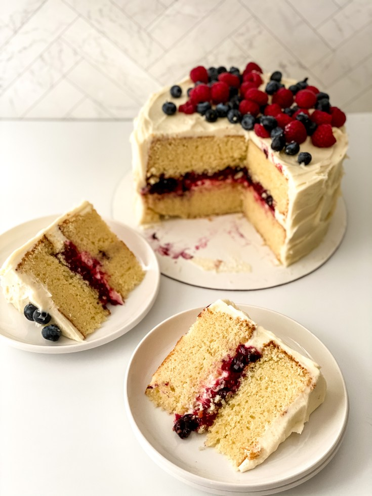 slices of mixed berry chantilly cake on circle white plates