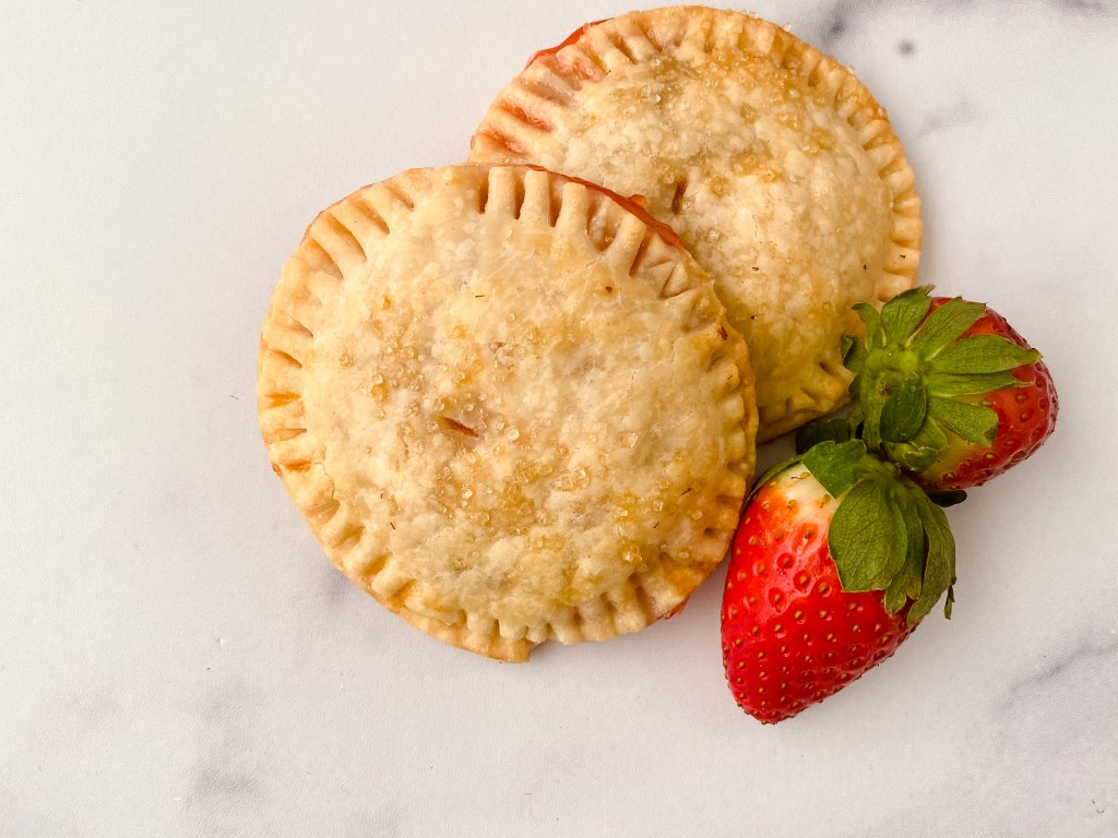 two strawberry hand pies with fresh strawberries