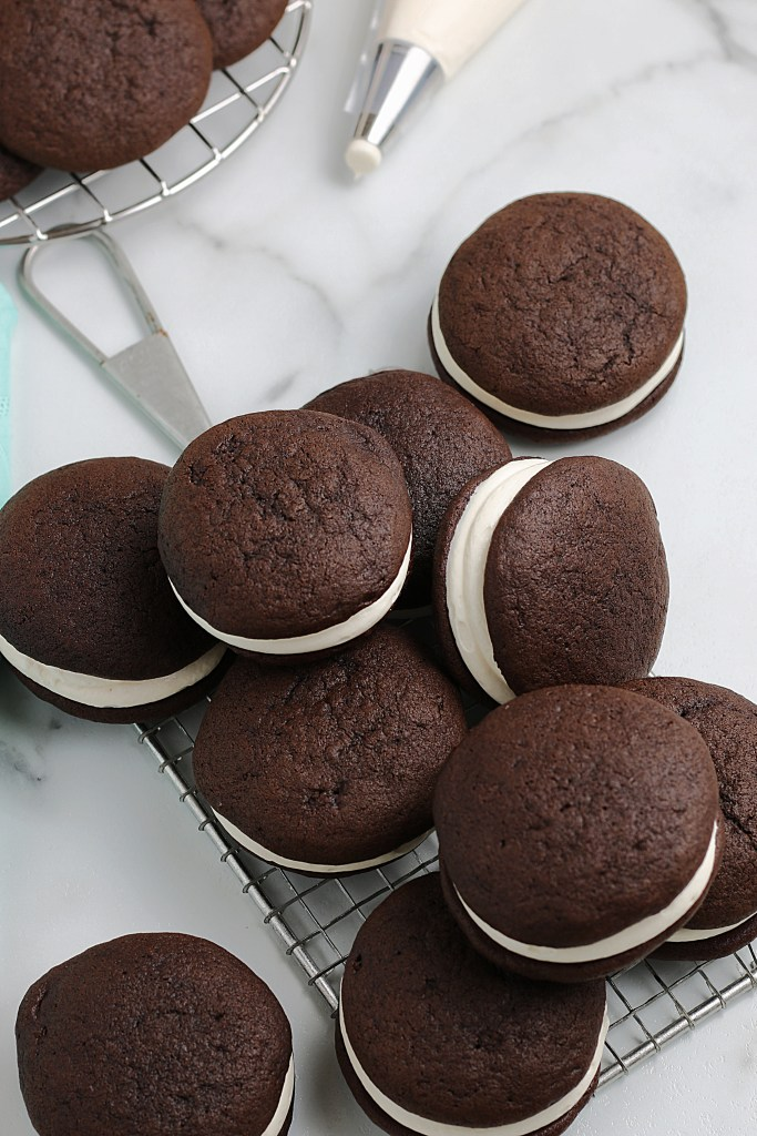 overhead shot of whoopie pie cookies scattered on a counter and cooling rack