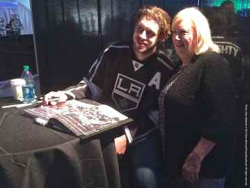 Center Anze Kopitar poses for a photo with a fan