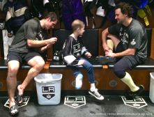 LA Kings rookie center Nick Shore (left) signs nine-year-old cancer patient Grace Bowen's jersey, while right wing Justin WIlliams (right) looks on.