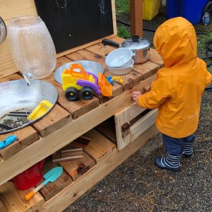 Mud kitchen in the rain, toys, water, raincoat in backyard