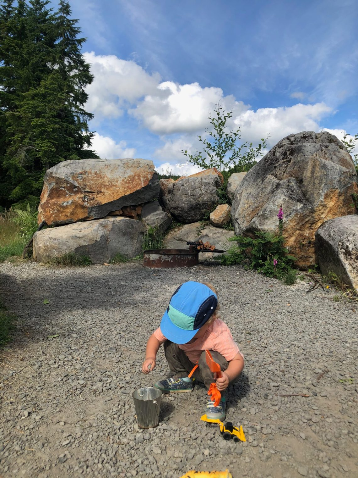 Campsite playing for a toddler is all about the rocks and dirt