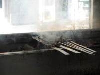 metal skewers with smoke cooking over a coal fire