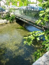 running water with a pedestrian bridge