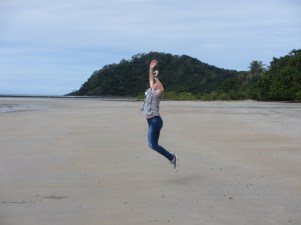 girl in blue jeans jumping in the air on the beach