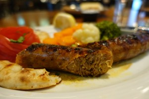 Grilled sausage cut in half and served with vegetables on a white plate
