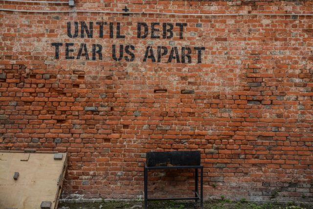 Graffiti on wall reads 'Until Debt Tear Us Apart' - Debt Sucks
