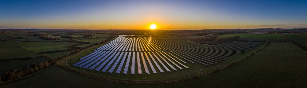 Panorama View of Solar Farm With Sunset in Behind