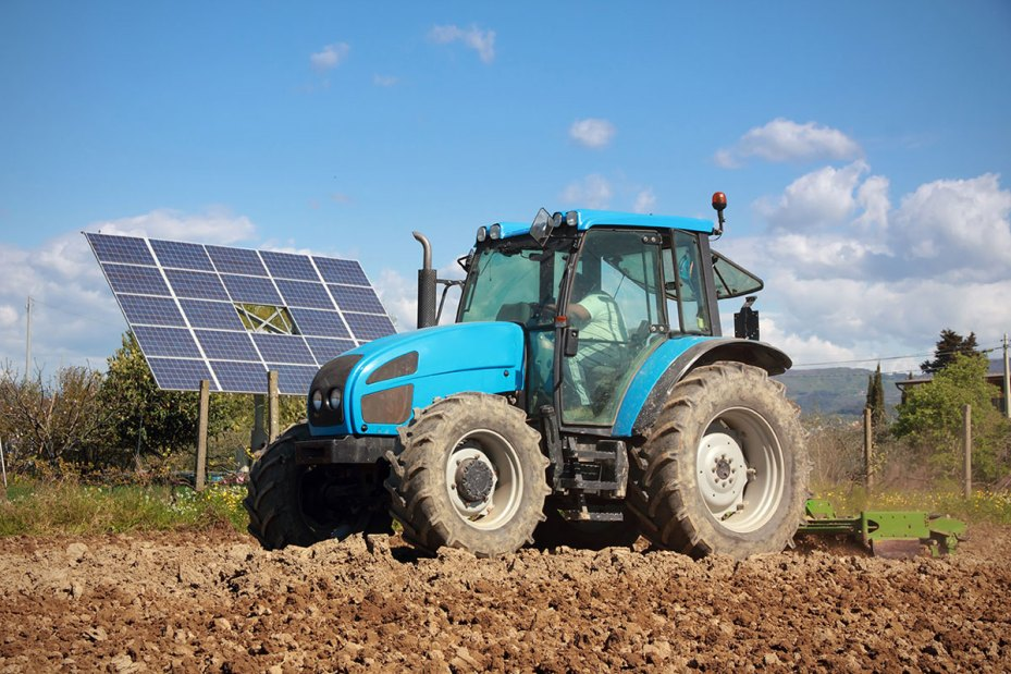 Blue Tractor in Foreground With Solar Panel in Behind on a Nice Day