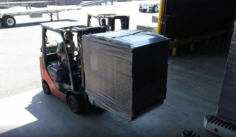 Male Worker Lifting Boxes With a Forklift and Stacking Them in Storage Area