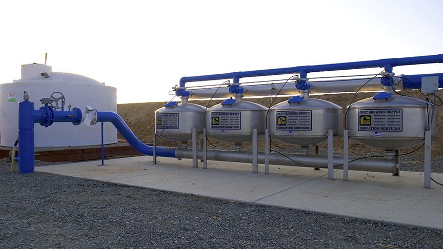 Water Filtration System With Four Large Cylinders Sitting on Flat Rocky Ground