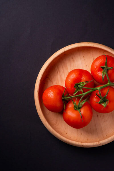 Five round red tomatoes on the stem in a wooden bowl