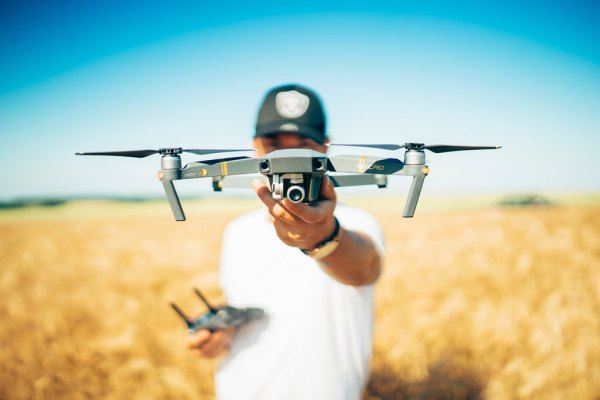 Man in wheat field holding drone