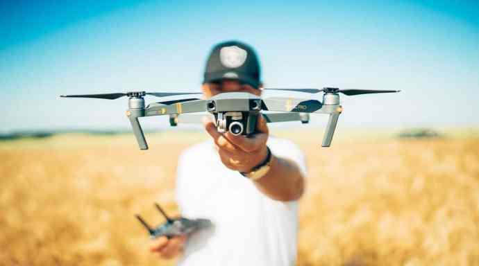 Man in wheat field holding drone