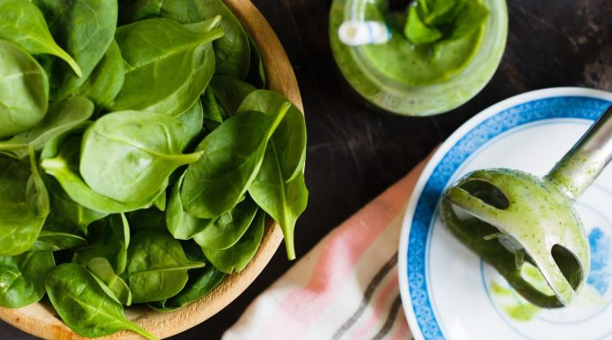 A bowl of loose spinach leaves and a hand blender with green residue.