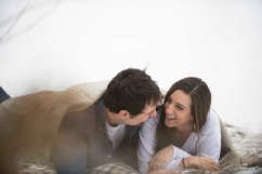 engagement portraits laughing on blanket in snow