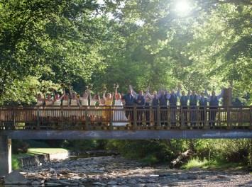 large bridal party celebrating on bridge outside of Mayernik Center