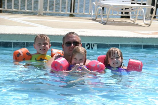 Dad and kids swimming in a pool.