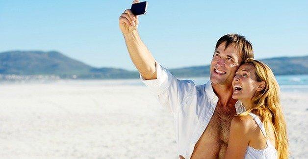 пара со смартфоном на пляже