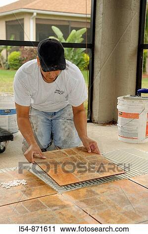 male hispanic lays ceramic tile on