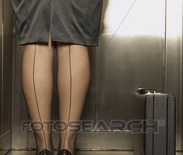 Rear View Of Businesswoman With Seamed Stockings Standing In Elevator